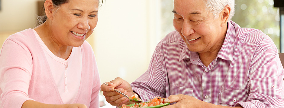 elderly asian couple eating dinner together