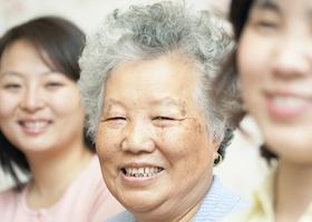 Elderly woman smiling at camera. Vertically framed shot.