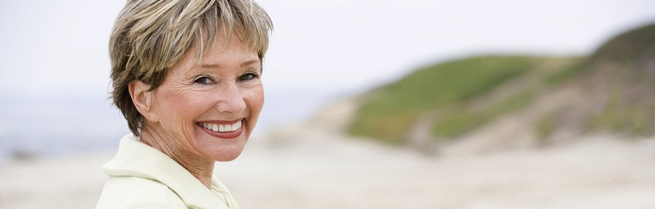 Woman stood on a beach smiling