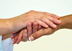 Two female hands clasped in compassionate hold