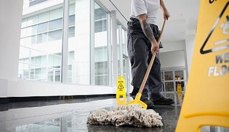 Office cleaner cleaning floor