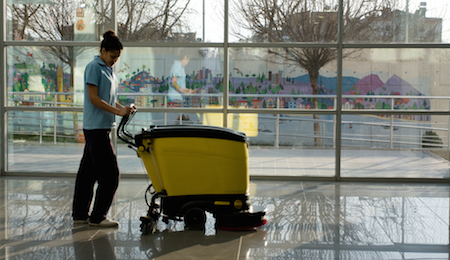 A worker is cleaning the floor with machine