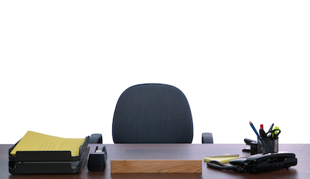 Desk with nobody sat at it against a white background. Blank name sign to add your own text.