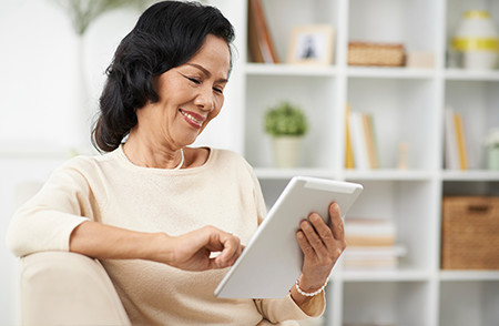 Smiling Woman is Seated Using a Tablet Device
