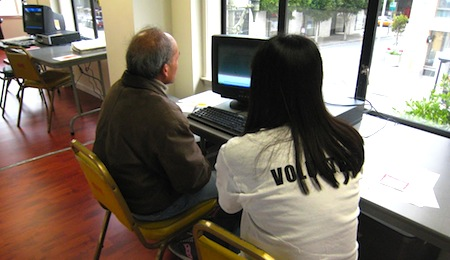 a volunteer helping with a senior on how to uses a computer